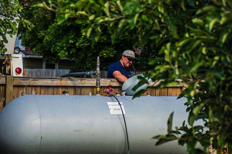 Man checking propane tank