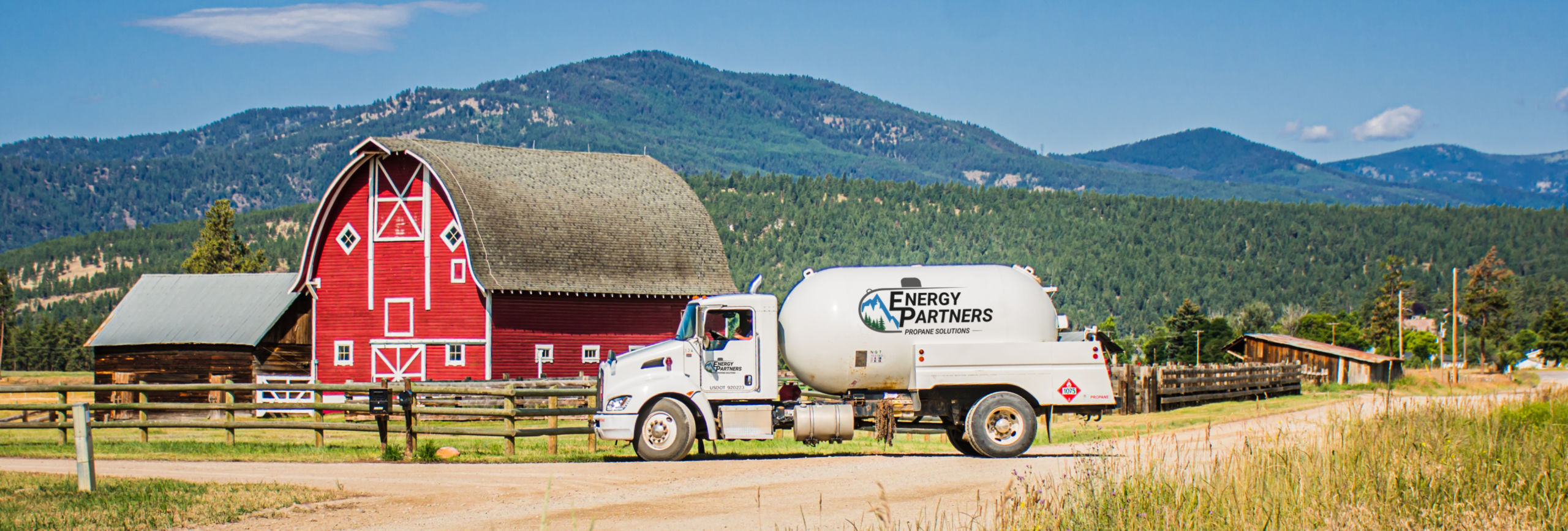 Energy Partners propane tank pulling up to barn with hills in the background